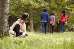 Fille de métis se mettant à genoux en parc pour attacher sa chaussure, sa famille marchant à l'arrière-plan, angle faible photographie stock libre de droits