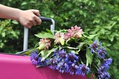 Fille de main avec une valise et des fleurs Images libres de droits