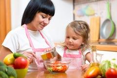Fille de maman et d'enfant préparant la nourriture saine Photo libre de droits