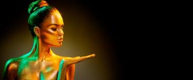 Fille de mannequin dans les étincelles d'or lumineuses colorées montrant le produit sur la main vide l'espace vide de copie image libre de droits
