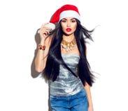 Fille de mannequin de Noël avec de longs cheveux droits de vol dans le chapeau rouge de Santa Image libre de droits