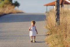 Fille de marche sur la route Photographie stock
