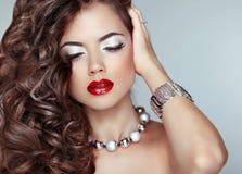 Fille de mode de beauté Long cheveu ondulé Languettes rouges Maquillage d'oeil bijou Image stock