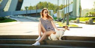 Fille de mode de hippie avec son chien dans la ville Image libre de droits