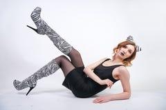 Fille de mode portant la petite robe noire du spandex avec des bottes de velours de z?bre avec des talons hauts sur le fond blanc photo stock