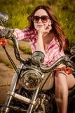 Fille de motard s'asseyant sur la moto Images stock