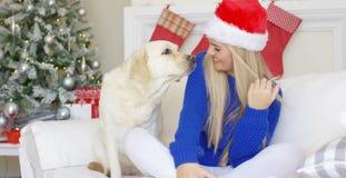 Fille de Noël avec son ami de chien au divan Photos stock