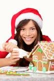 Fille de Noël effectuant la maison de pain d'épice Photo libre de droits