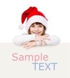 Fille de Noël heureux avec le chapeau de Santa derrière le conseil blanc Photos stock