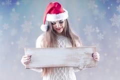 Fille de Noël tenant un conseil en bois vide pour le texte Photographie stock libre de droits