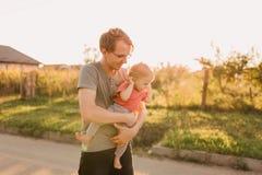Fille de père et de bébé dehors dans le coucher du soleil Image stock