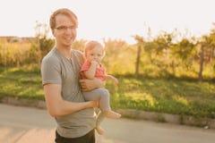 Fille de père et de bébé dehors dans le coucher du soleil Photo stock