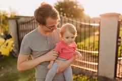 Fille de père et de bébé dehors dans le coucher du soleil Images stock