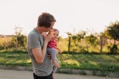Fille de père et de bébé dehors dans le coucher du soleil Photos stock