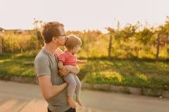 Fille de père et de bébé dehors dans le coucher du soleil Photographie stock libre de droits