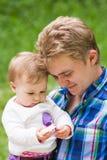 Fille de père et de bébé jouant en parc Photo stock