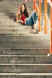 Fille de patin sur des escaliers avec la planche à roulettes Image libre de droits