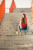 Fille de patin sur des escaliers avec la planche à roulettes Image stock