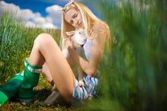 Fille de pays avec une petite chèvre dans des ses mains Photographie stock
