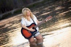 Fille de pays jouant la guitare acoustique en rivière Image stock