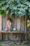 Fille de pays s'asseyant sous la vigne Fille jouant avec son jouet Photo libre de droits