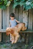 Fille de pays s'asseyant sur un banc avec son chien sous la vigne En bois Photos stock