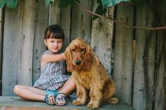 Fille de pays s'asseyant sur un banc avec son chien sous la vigne En bois Images libres de droits