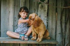 Fille de pays s'asseyant sur un banc avec son chien sous la vigne En bois Image stock
