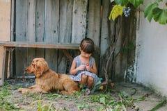 Fille de pays s'asseyant sur un banc avec son chien sous la vigne En bois Photo libre de droits
