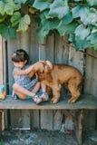 Fille de pays s'asseyant sur un banc avec son chien sous la vigne En bois Image libre de droits