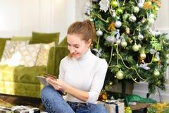 Fille de peintre à l'aide du smartphone pour souhaiter la bonne année aux amis Images stock