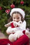 Fille de petit enfant étreignant son jouet pelucheux de renne près de Chris photos stock