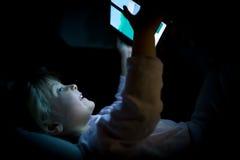 Fille de petit enfant employant la technologie de comprimé dans le lit par nuit à la maison Fille heureuse d'enfant dans le film  Photos libres de droits