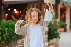 Fille de petit enfant souhaitant la bienvenue à des invités à la maison de campagne confortable de soirée Photos stock