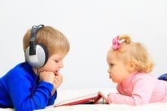 Fille de petit garçon et d'enfant en bas âge avec le casque utilisant Image stock