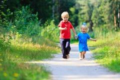 Fille de petit garçon et d'enfant en bas âge courant dans la forêt d'été Photographie stock