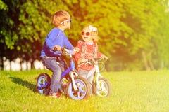 Fille de petit garçon et d'enfant en bas âge sur des vélos en été Photo libre de droits