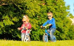 Fille de petit garçon et d'enfant en bas âge sur des vélos en été Photo stock