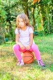 Fille de peu sept ans s'asseyant sur la boule photo stock