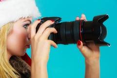 Fille de photographe en images de tir de chapeau du père noël Photographie stock