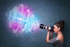 Fille de photographe faisant des photos avec le faisceau lumineux puissant photos stock