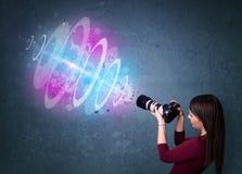 Fille de photographe faisant des photos avec le faisceau lumineux puissant images stock