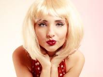 Fille de pin-up dans la rétro robe de perruque blonde soufflant un baiser Photographie stock libre de droits