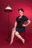 Fille de pin-up dans la robe noire avec la lampe Photo stock