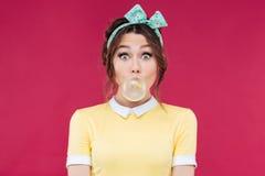 Fille de pin-up mignonne stupéfaite soufflant un ballon de bubble-gum Photos stock