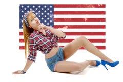 Fille de pin-up s'asseyant sur le plancher avec un drapeau des USA à l'arrière-plan photos libres de droits