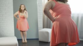 Fille de poids excessif s'habillant devant le miroir, satisfaisant avec l'aspect banque de vidéos