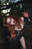 Fille de portrait avec les cheveux rouges et le vampire ensanglanté de visage, meurtrier, psychopathe, thème de Halloween, femme  Photographie stock