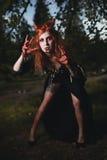 Fille de portrait avec les cheveux rouges et le vampire ensanglanté de visage, meurtrier, psychopathe, thème de Halloween, femme  Image libre de droits