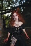 Fille de portrait avec les cheveux rouges et le vampire ensanglanté de visage, meurtrier, psychopathe, thème de Halloween, femme  Photo stock